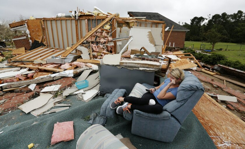 """Hilary Benjamin sits in a recliner that belongs to her good friends Julie and John Bercik, after what is believed to be a tornado hit their house on Sonny Boy Lane in Johns Island, S.C., Friday, Sept. 25, 2015. """"I've been in this chair so any times, it's just weird to sit in it like this"""", Benjamin said before helping the Berciks' clean up their house. Officials from the National Weather Service planned to walk through the neighborhood on Johns Island about a dozen miles west of Charleston to determine if the damage was from a tornado. (AP Photo/Mic Smith)"""
