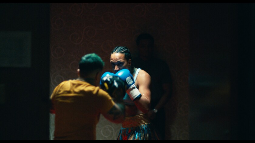A woman holds up her hands in boxing gloves as she faces a sparring partner.