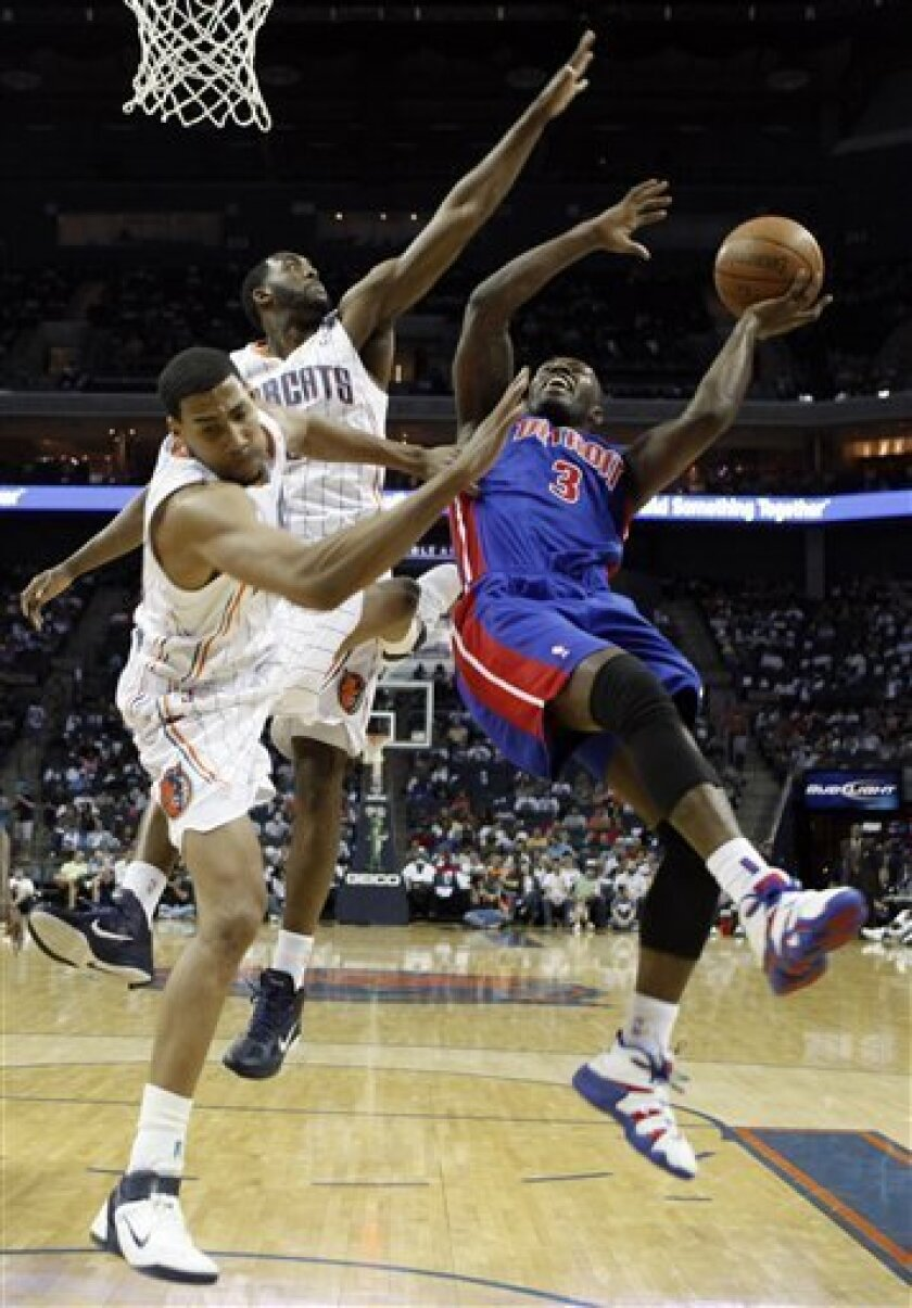 Detroit Pistons' Rodney Stuckey, right, is fouled as he drives past Charlotte Bobcats' D.J. White, back, and Garrett Temple, left, in the first half of an NBA basketball game in Charlotte, N.C., Sunday, April 10, 2011. (AP Photo/Chuck Burton)