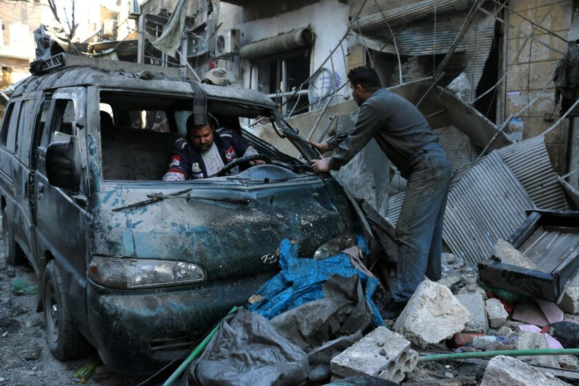 People inspect a damaged vehicle after a reported airstrike by Syrian government forces in the northern city of Aleppo on Saturday. In eastern Syria, Islamic State militants reportedly kidnapped hundreds of civilians.