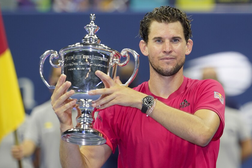 FILE - Dominic Thiem, of Austria, holds up the championship trophy after defeating Alexander Zverev, of Germany, in the men's singles final of the U.S. Open tennis championships in New York, in this Sunday, Sept. 13, 2020, file photo. Defending champion Dominic Thiem has pulled out of the U.S. Open, saying Wednesday, Aug. 18, 2021, he will miss the rest of the year because of a right wrist injury. (AP Photo/Frank Franklin II, File)
