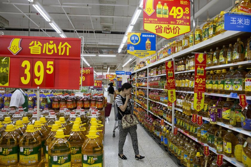 "In this Tuesday, Nov. 10, 2015, photo, a shopper looks at products at a Wal-Mart in Shenzhen, in southern China's Guangdong province. Wal-Mart's ""Worry Free"" message uses the Chinese characters for ""save, heart, price,'' seen on the red signs, implying quality and reassuring shoppers who worry that"