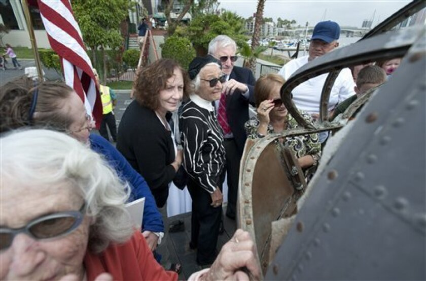 Linda Oliver, center, widow of Richard Oliver, one of the original bombadiers of the Swamp Ghost, a B-17E bomber which crashed in a Papua New Guinea swamp during World War II, examines the recently restored and recovered plane at its unveiling ceremony in Long Beach, Calif., on Friday, June 11, 2010. (AP Photo/Adam Lau)