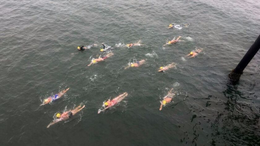 Athletes swim to cross the border from the United States into Mexico.