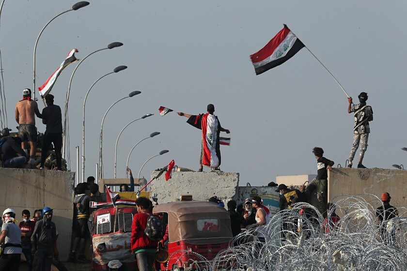 Iraqi anti-government protesters climb on walls and barriers set by security forces Oct. 31 near Baghdad's Green Zone.