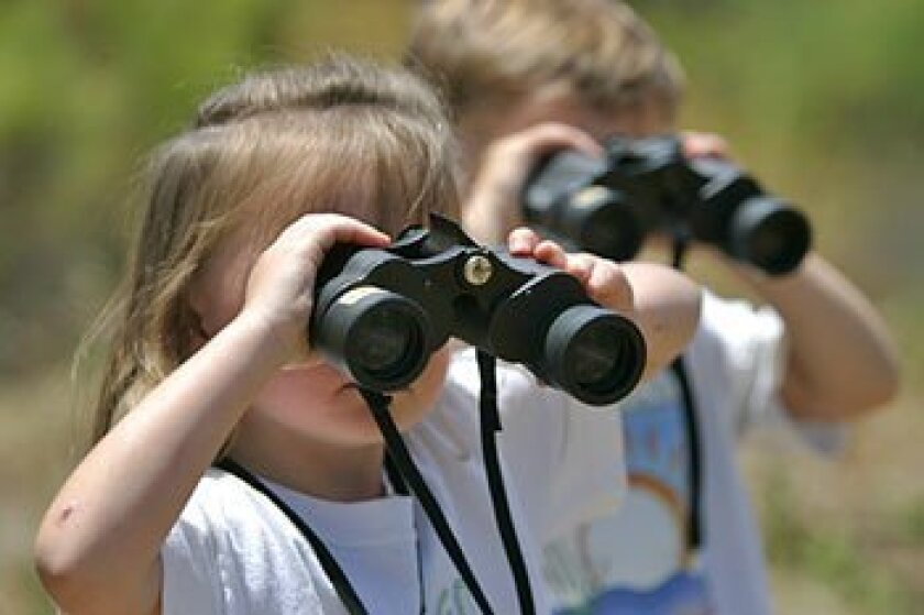 Julia (left) and Jack Ryan of Alpine used binoculars yesterday to look at the San Diego River.  (Nancee E. Lewis / Union-Tribune)