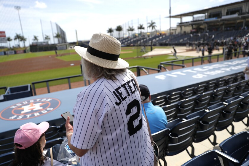 A woman wears a Derek Jeter as she settles into her seat prior to a spring training baseball game between the New York Yankees and the Washington Nationals, Thursday, March 12, 2020, in West Palm Beach, Fla. (AP Photo/Julio Cortez)