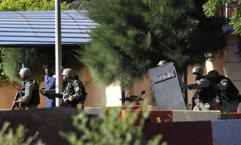 Malian troops take position outside the Radisson Blu hotel in Bamako. Gunmen went on a shooting rampage at the luxury hotel in Mali's capital, seizing 170 guests and staff. At least three people are dead.
