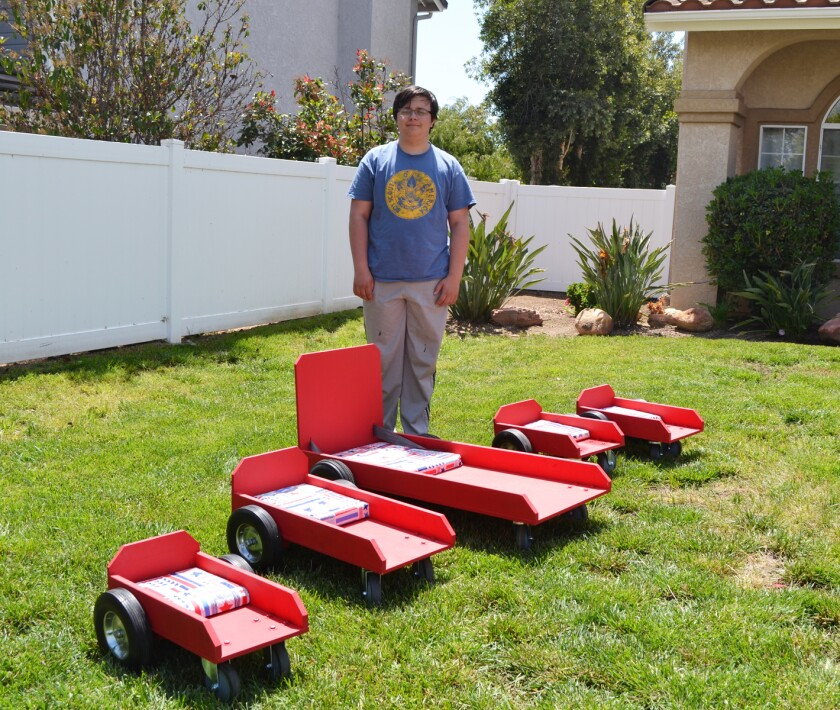 Eagle Scout Aidan Friend with the five caster cart wheelchairs he made for children in Mexico.