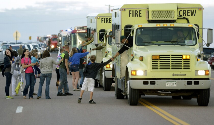 Supporters greet fire crews as they return from their shifts from fighting the Black Forest wildfire outside a fire camp at Pine Creek High School in Colorado Springs, Colo., on Sunday.