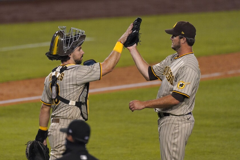 Padres catcher Austin Hedges and relief pitcher Drew Pomeranz celebrate after Pomeranz pitched a perfect ninth inning.