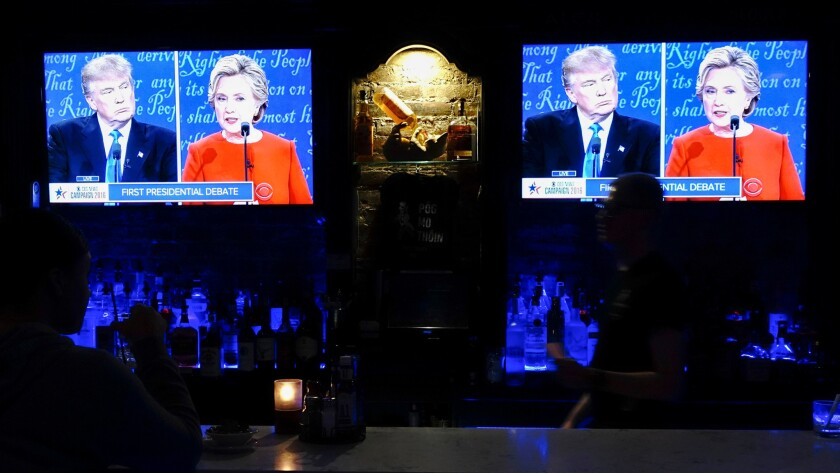 People watch the first presidential debate on a television on Sept. 26 in a New York bar.