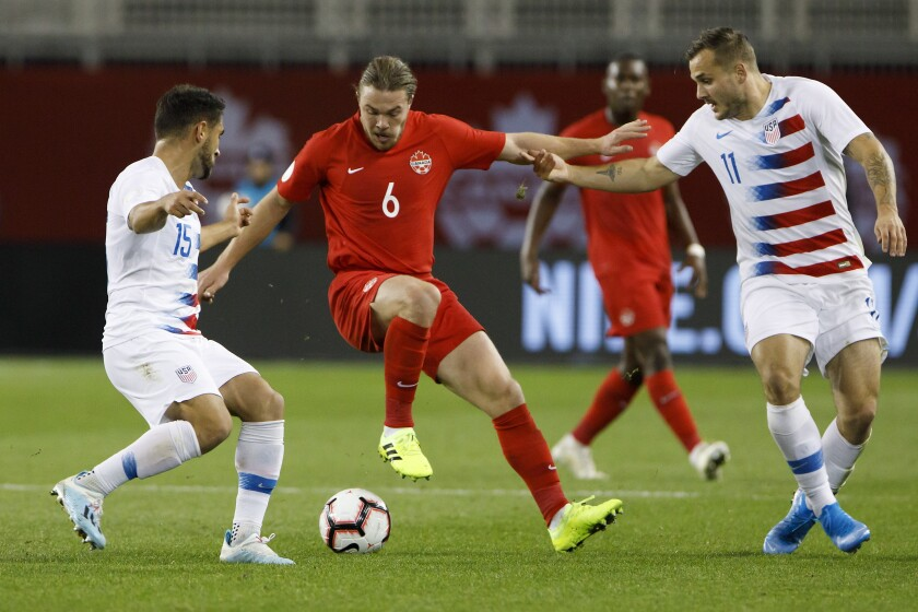 Canada midfielder Samuel Piette (6) tries to fend off U.S. midfielder Cristian Roldan (15) and forward Jordan Morris (11) during the first half of a CONCACAF Nations League match on Tuesday.