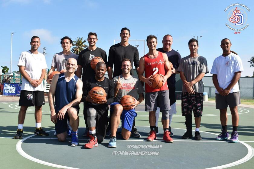 Sneaks Summer Classic co-founders Sawsun Khodapanah (far left) and Tyson Youngs (far right) pose with 2019 tournament winners, The 5 O'Clock Bandits team, and their customized prize basketballs, during the second annual Sneaks Summer Classic basketball tournament held July 6, 2019 at La Jolla Recreation Center