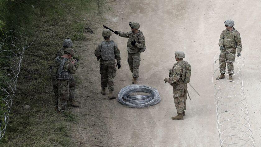 Members of the U.S.military place razor wire along the U.S.-Mexico border near the McAllen-Hidalgo I