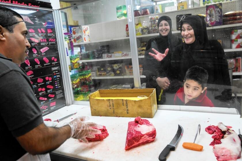 Regular customer Kathy Farhat, far right, jokes with Leonardo Castañeda, left, as Maison Saab and her son, Ali Saab, 4, look on at Fatima's Halal Meat Market in Bell.