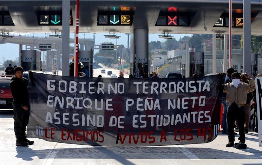 Estudiantes y padres de los 43 jóvenes desaparecidos de Ayotzinapa se manifiestan hoy, domingo 25 de diciembre de 2016, en una caseta de peaje en Ciudad de México (México), como parte de una caravana que inició el martes en el estado de Guerrero y que concluirá mañana con una visita a la Basílica de Guadalupe en la capital mexicana. EFE