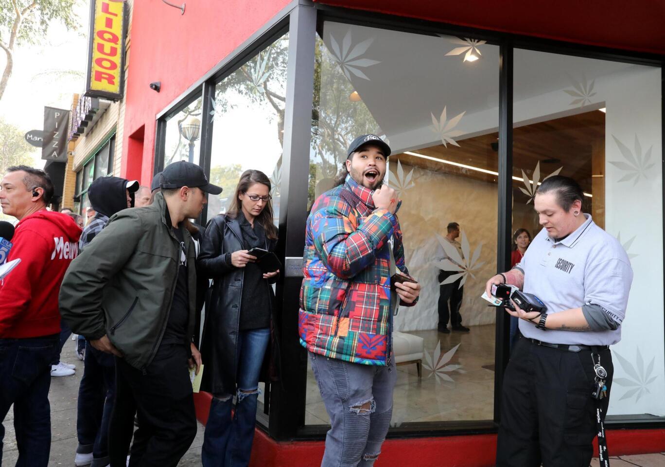 Josh De La Cruz (c) reacciona después de haber escaneado su licencia de conducir para ser la primera persona autorizada en el dispensario MedMen para comprar productos de marihuana recreativa en West Hollywood, California.