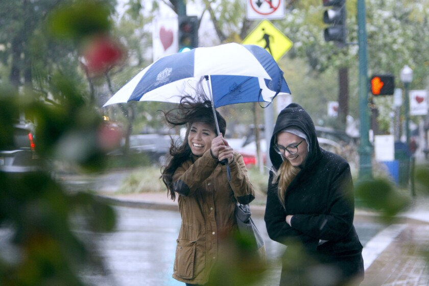 Felicia Schliewe, 31 of Highland Park, left, and Daniella Langley, 24 of Lake View Terrace, get hit by a gust of wind as they walk on a rainy afternoon on Honolulu Avenue and Ocean View Avenue in Montrose, on Friday, Feb. 17, 2017. A massive storm hit the Southland over the weekend.