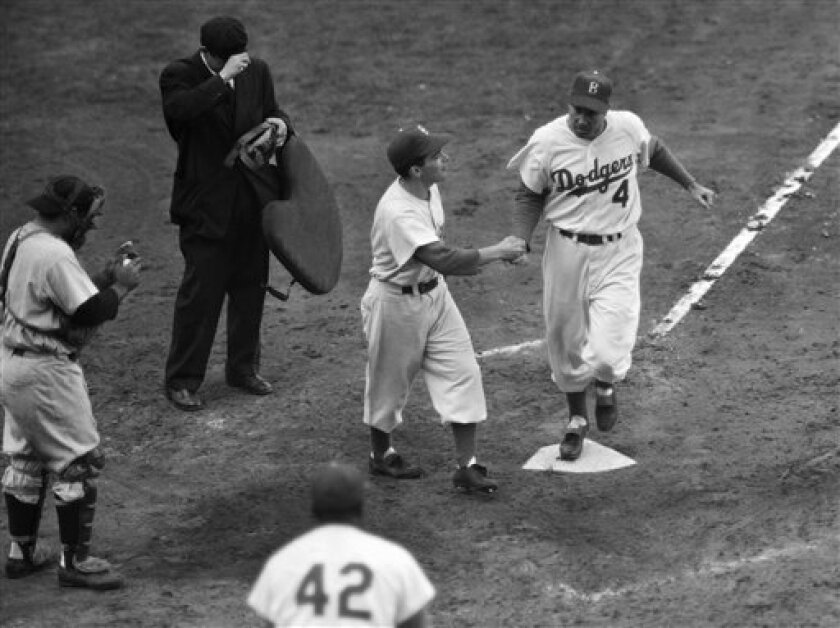 FILE - In this Oct. 6, 1952, file photo, Brooklyn Dodgers' Duke Snider is greeted by the batboy on his second homer of Game 6 of baseball's World Series against the New York Yankees at Ebbets Field in the Brooklyn borough of New York. Snider, 84, died early Sunday, Feb. 27, 2011, of what the family