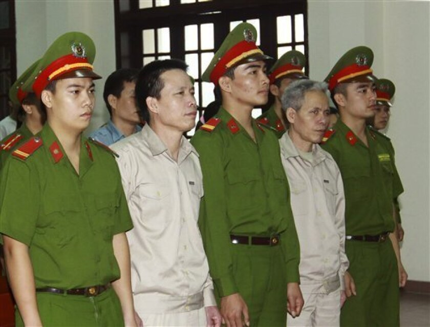 FILE - In this April 2, 2013 file photo, Doan Van Vuon, second from left and his brother Doan Van Sinh, fourth from left, stand trial at the court in the northern city of Haiphong, Vietnam.  Vuon was sentenced Friday, April 5, 2013,  to five years in jail for attempted murder and his three other re