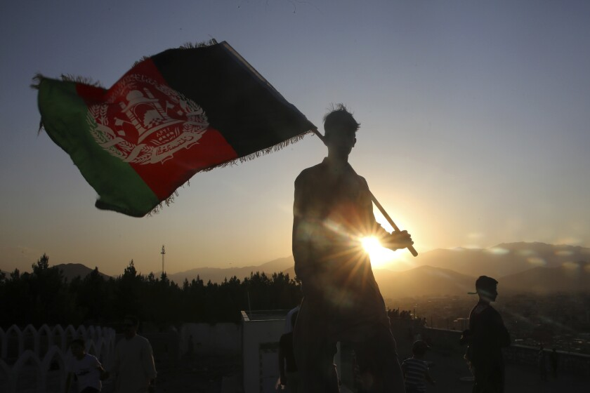 FILE - In this Aug. 19, 2019, file photo, a man waves an Afghan flag during Independence Day celebrations in Kabul, Afghanistan. An Afghan official Sunday, Feb. 9, 2020, said multiple U.S. military deaths have been reported in Afghanistan's Nangarhar province after an insider attack by a man wearing an Afghan army uniform. (AP Photo/Rafiq Maqbool, File)