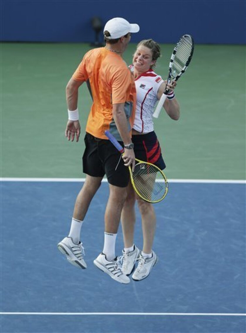 Belgium's Kim Clijsters, right, and Bob Bryan celebrate after their mixed doubles match against Irina Falconi and Steve Johnson in the third round of play at the 2012 US Open tennis tournament, Friday, Aug. 31, 2012, in New York. (AP Photo/Charles Krupa)