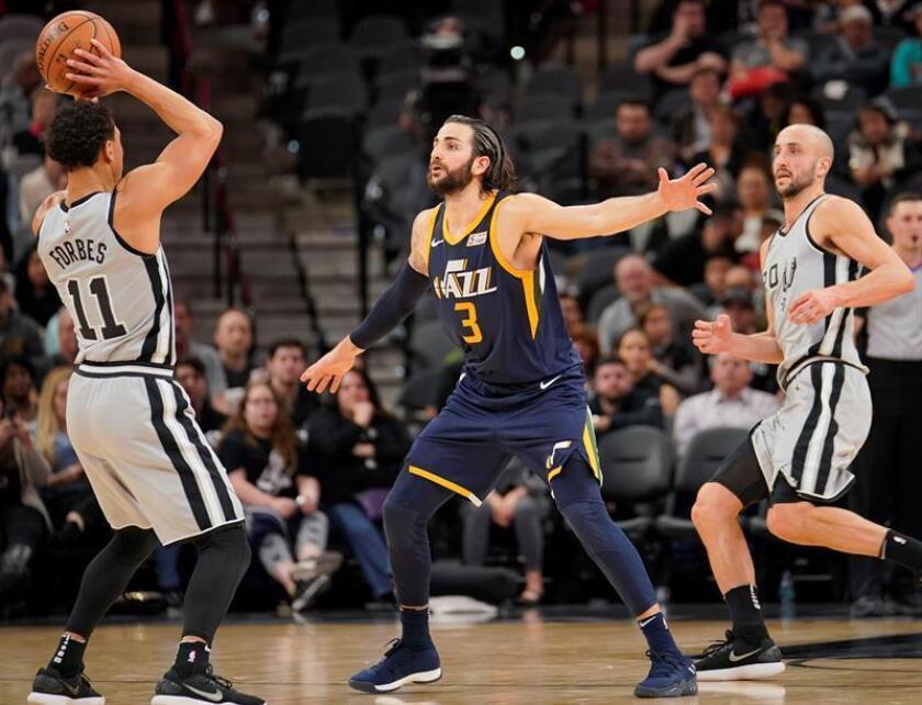 Ricky Rubio (c) de Utah Jazz en acción contra Bryn Forbes (i) y Manu Ginobili (d) de San Antonio Spurs durante el partido de baloncesto de la NBA disputado este sábado, en San Antonio, Texas (EE.UU.). EFE