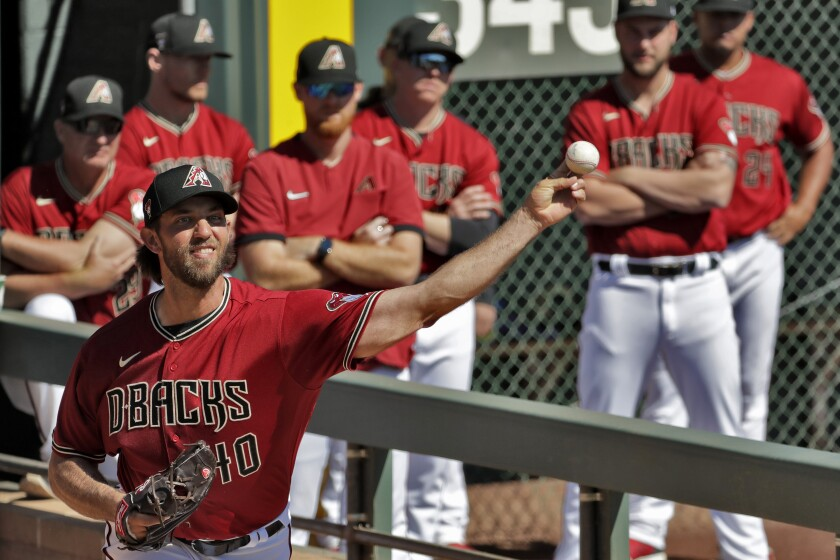 Arizona Diamondbacks pitcher Madison Bumgarner warms up as teammates look on prior to a spring training baseball game against the Cincinnati Reds, Thursday, Feb. 27, 2020, in Scottsdale Ariz. (AP Photo/Matt York)
