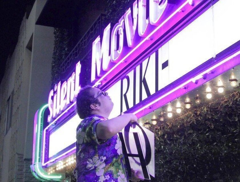 """Mark Ayala puts up the movie title on the marquee before the midnight showing of the movie """"Riki-Oh"""" at the Cinefamily on Fairfax Avenue in Los Angeles on April 26, 2013."""
