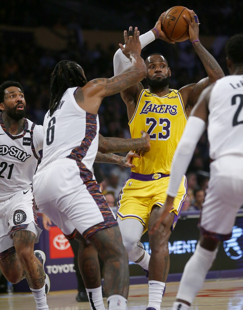 LeBron James makes a pass as he drives down the lane against the Nets during the second quarter March 10 at Staples Center.
