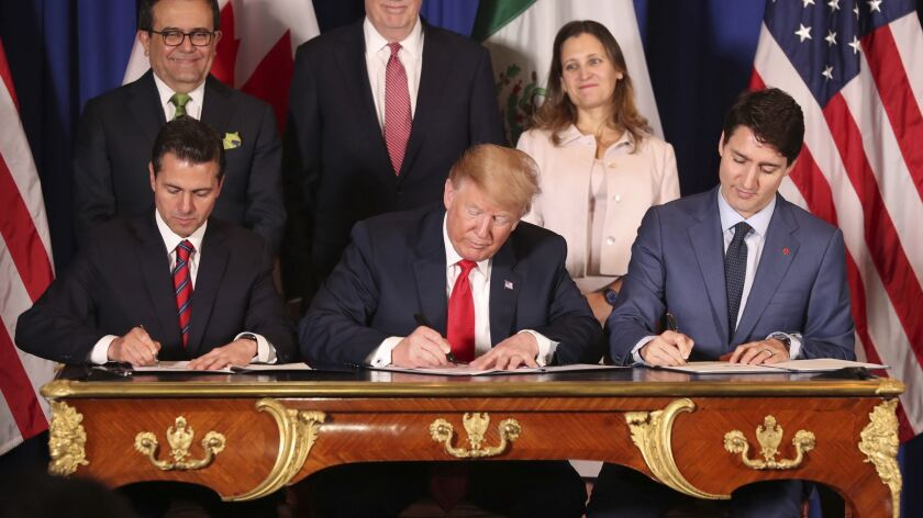Mexican President Enrique Peña Nieto, left, President Trump and Canadian Prime Minister Justin Trudeau sign their countries' new trade deal Nov. 30. The deal is awaiting approval from the countries' legislatures.
