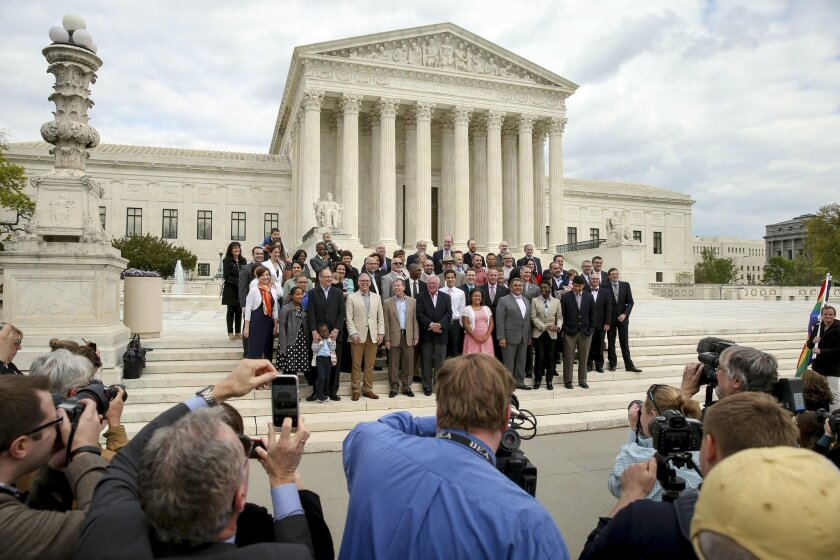 Plaintiffs from Tennessee, Michigan, and Ohio pose for photographs with the lawyers representing them in front of the Supreme Court on April 27.