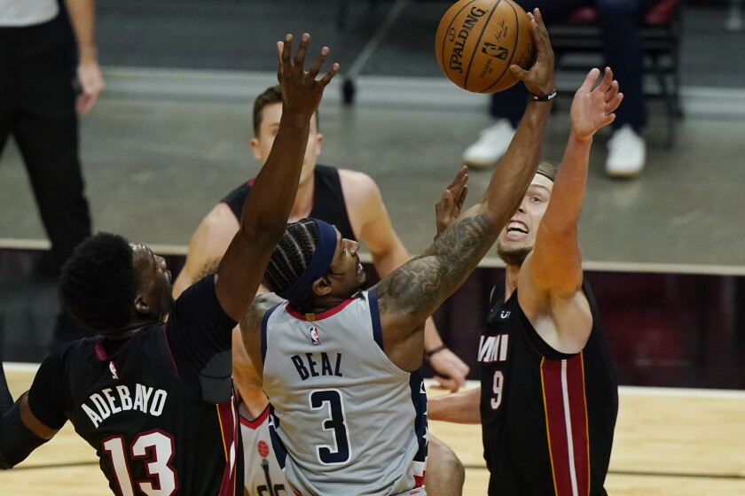 Washington Wizards guard Bradley Beal (3) drives to the basket as Miami Heat forward Kelly Olynyk (9) and center Bam Adebayo (13) defend during the first half of an NBA basketball game, Friday, Feb. 5, 2021, in Miami. (AP Photo/Marta Lavandier)