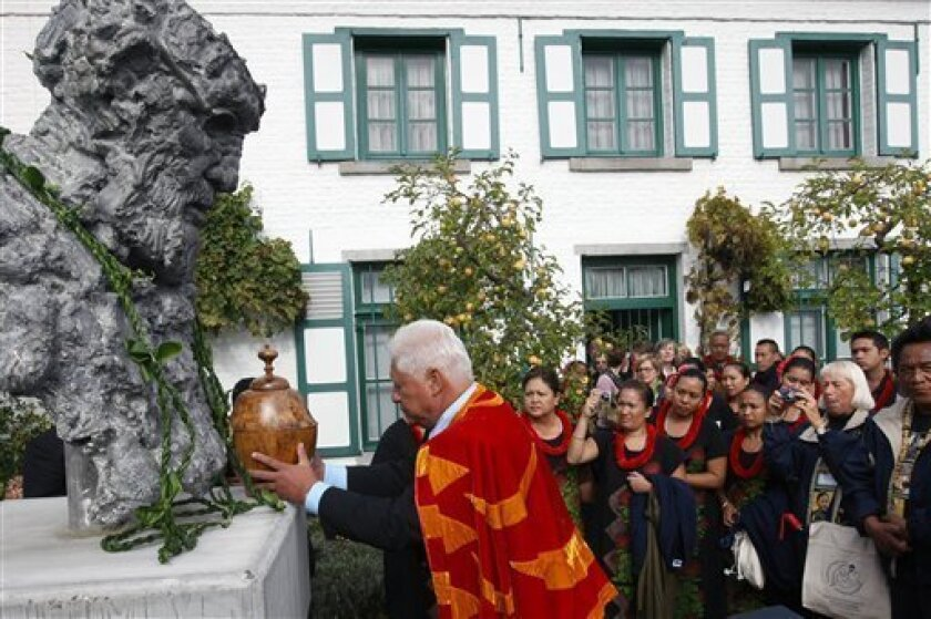 People from Molokai, Hawaii, stand around a statue depicting Father Damien in the garden of his birthplace in Tremelo, Belgium, Sunday Oct. 4, 2008. A mass attended by Belgian royals and government as well as the bishop of Honolulu among others, celebrated a 19th century local hero Sunday, who cared for leprosy sufferers on the Hawaiian island of Molokai until the disease took his life in 1889, and will become a saint for his work.(AP Photo/Geert Vanden Wijngaert)
