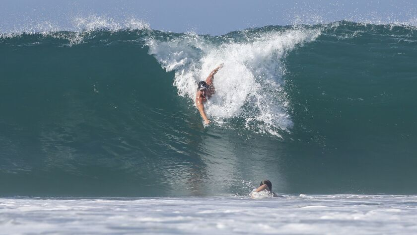 Kevin Walsh catches a big wave during the second heat as another bodysurfer prepares to dive under the wave.