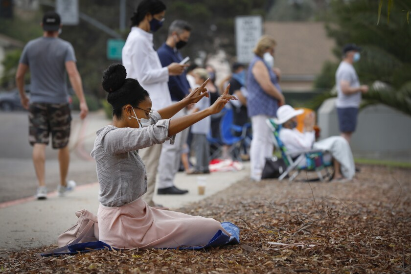 Jai Santos prays outside Mt. Carmel High School.