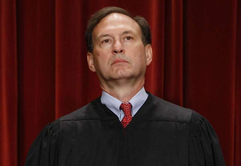 Justice Samuel A. Alito Jr. in black robes in front of a red curtain