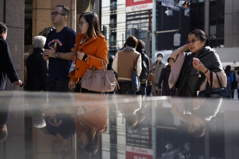 Pedestrians walk through Ginza shopping district in Tokyo on Monday. According to the government, the Japanese economy recorded its first growth in three quarters as it expanded at an annualized rate of 2.2% in the fourth quarter.