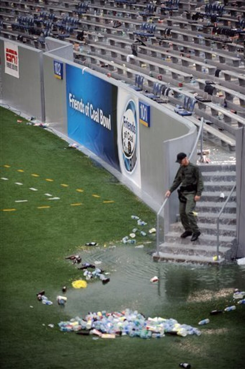A law enforcement officer walks through an empty stadium during a weather delay at the West Virginia and Marshall NCAA college football game, Sunday, Sept. 4, 2011, in Morgantown, W.Va. (AP Photo/Jeff Gentner)