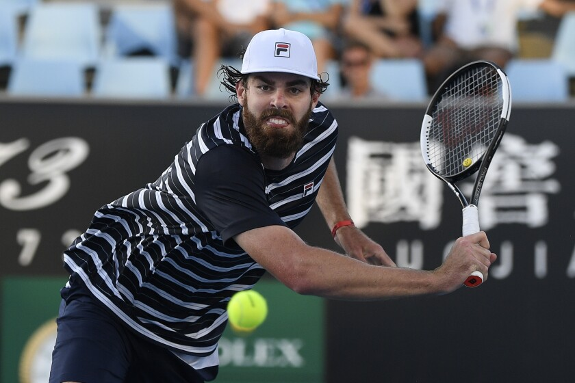 """FILE - American Reilly Opelka makes a backhand return to compatriot Taylor Fritz during their second round match at the Australian Open tennis championship in Melbourne, Australia, in this Wednesday, Feb. 10, 2021, file photo. Opelka is back to winning matches at the Italian Open after dealing with a bout of COVID-19 that he said kept him off the court entirely for more than two weeks and prevented him from practicing the way he usually does for nearly a month.""""It felt like a rough flu,"""" Opelka said in a telephone interview Tuesday, May 11, 2021, from Rome, where he beat Lorenzo Musetti of Italy 6-4, 6-4 to reach the round of 16 at the clay-court tournament. (AP Photo/Andy Brownbill, File)"""