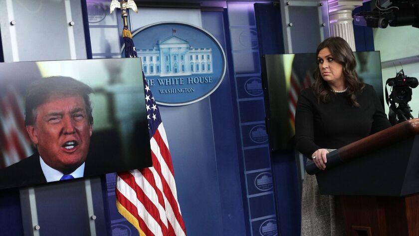 President Trump speaks via video as White House Press Secretary Sarah Sanders listens during a daily news briefing.
