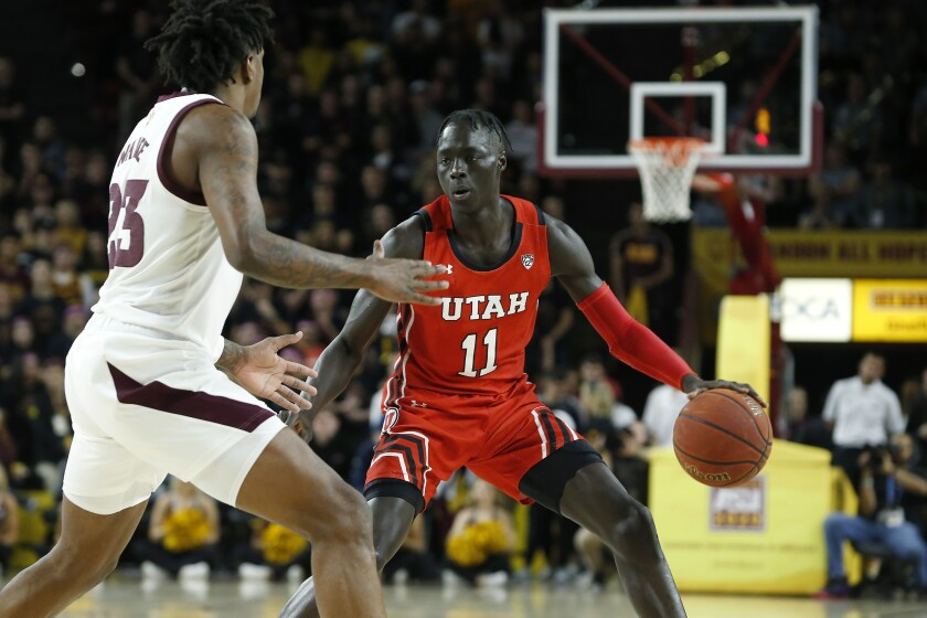 FILE - Utah guard Both Gach (11) advances the ball up-court while Arizona State's Romello White (23) defends during the first half of an NCAA college basketball game in Tempe, Ariz., in this Saturday, Jan. 18, 2020, file photo. Gach switched schools to be closer to his family during the COVID-19 pandemic. Now at Minnesota, the junior guard has been granted immediate eligibility by the NCAA.(AP Photo/Ralph Freso, File)