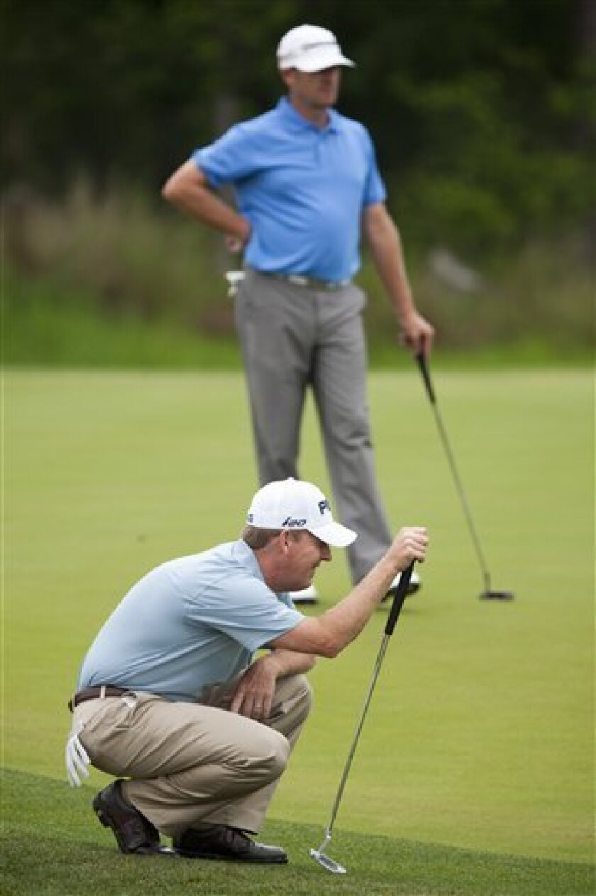 Jeff Maggert, in foreground, checks the green on the eighth hole during the second round of the Houston Open golf tournament, Saturday, March 31, 2012, in Humble, Texas. (AP Photo/Eric Kayne)