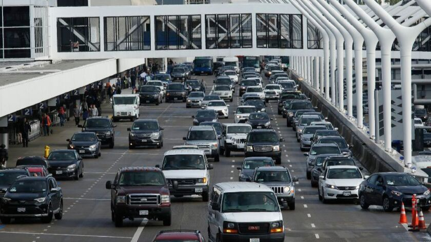 Traffic is bumper to bumper on the departure deck as travelers do the holiday shuffle at Los Angeles International Airport.