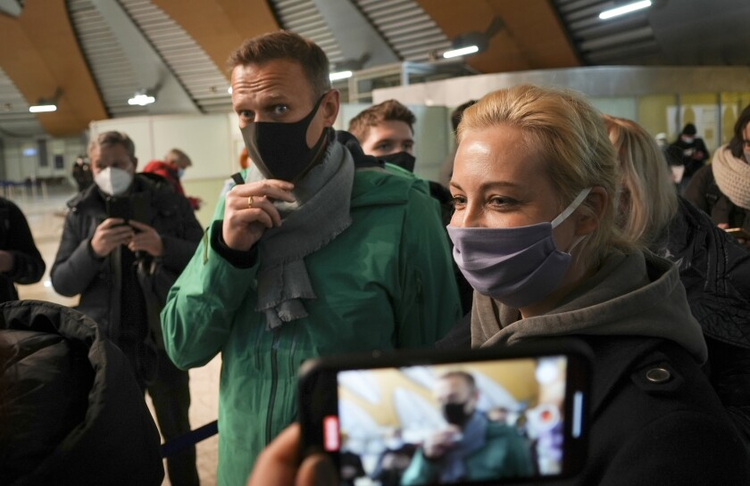 Alexei Navalny and his wife, Yulia, wear masks as they stand in line