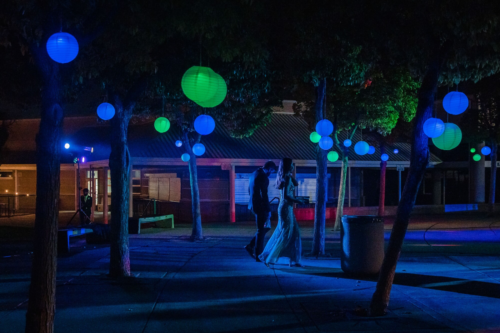 Students walk through a decorative area at their prom held outside at Eastlake High School in Chula Vista on May 8, 2021.