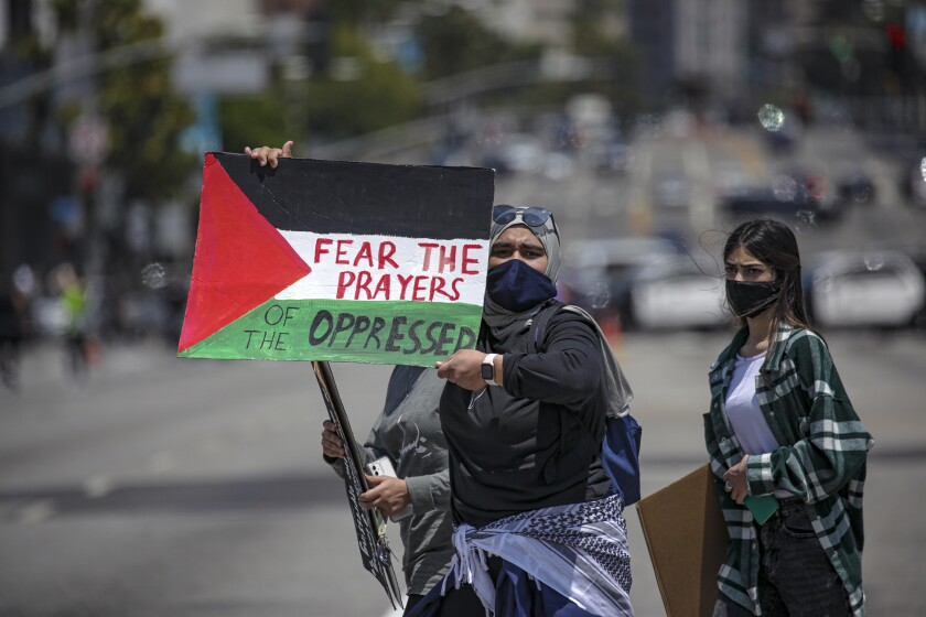 """A protester holds a sign that says """"Fear the prayers of the oppressed."""""""