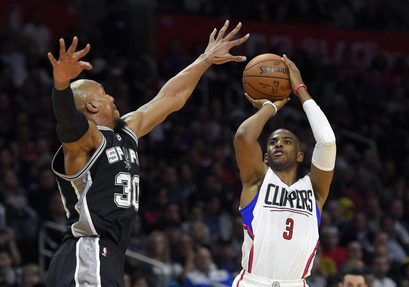 Los Angeles Clippers guard Chris Paul, right, shoots as San Antonio Spurs forward David West defends during the second half of an NBA basketball game Thursday, Feb. 18, 2016, in Los Angeles. The Clippers won 105-86. (AP Photo/Mark J. Terrill)