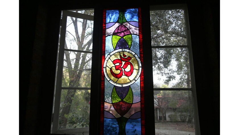 A stain glass window with the colorful Om symbol in the lecture hall at the Ramakrishna Monastery in